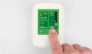 Mão configurando monitor de qualidade do ar IAQPoint2.